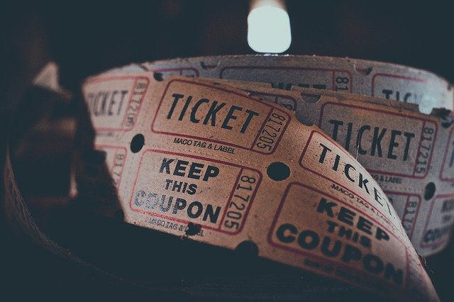 Person holding a bunch of tickets and coupons