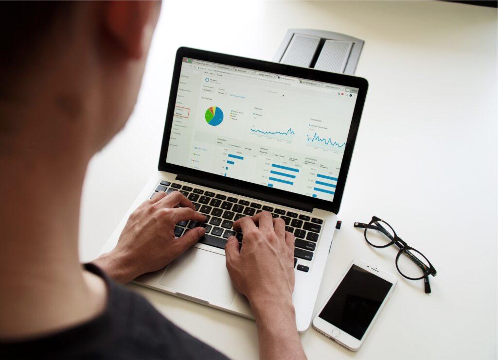 Man on a laptop watching analytics and statistics