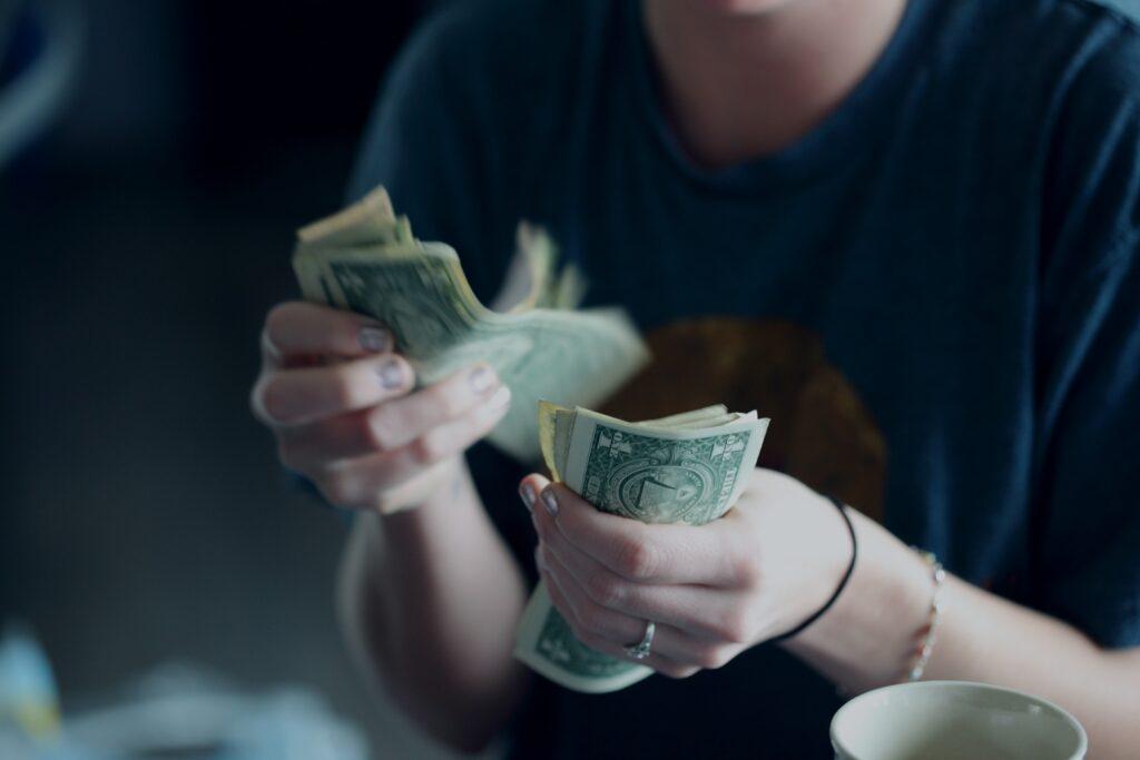 A twenty-four year old woman counting dollar bills