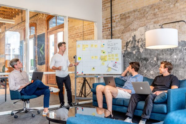 men discussing sitting with laptops whiteboard post its