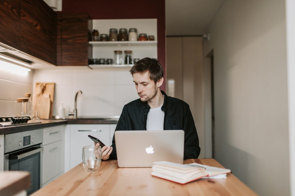 Man looking at smartphone laptop screen open, in kitchen